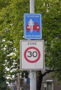 "The sign reads ""Bike Street. Cars are guests"""